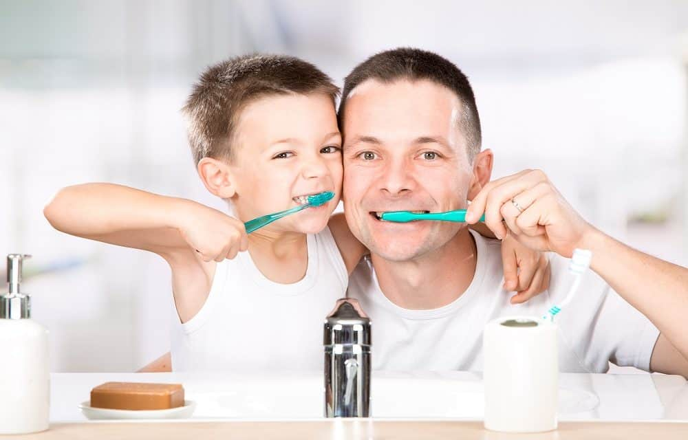 father and son brushing teeth together