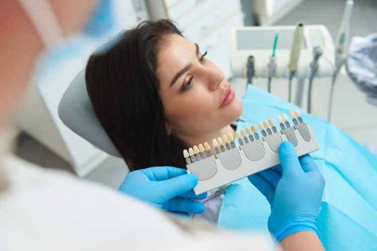 As a part of the dental crown procedure, this image shows someone matching the color of a patient's natural teeth.